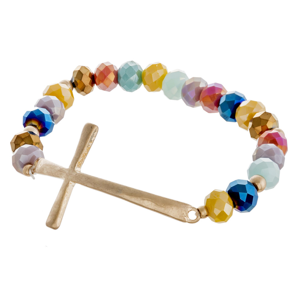 Faceted beaded stretch bracelet featuring an east west cross focal